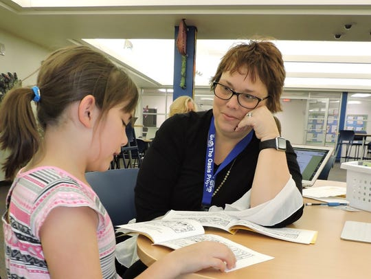 One of Oasis Project's volunteer tutors, Deanna Schadeberg, works with a student during one of the group's tutoring sessions.
