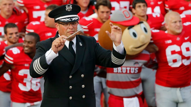 "In this Sept. 7, 2013 file photo, Ohio State University marching band director Jon Waters leads the band in ""Carmen Ohio"" following a NCAA football game against San Diego State at Ohio Stadium in Columbus, Ohio."