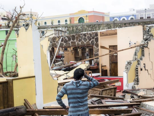 A person looks at damaged homes in the La Perla neighborhood