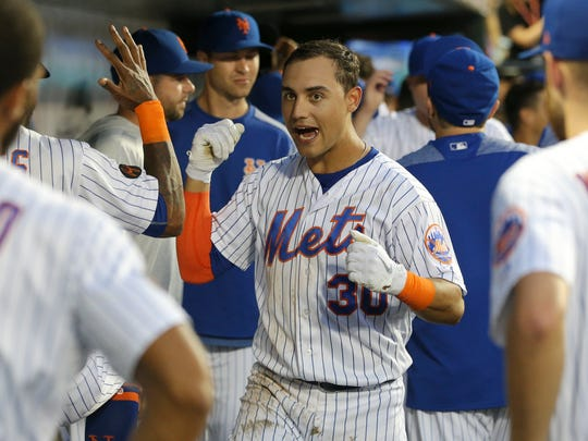 New York Mets left fielder Michael Conforto (30) celebrates in the dugout with teammates after hitting a two-run home run against the San Diego Padres during the third inning at Citi Field.