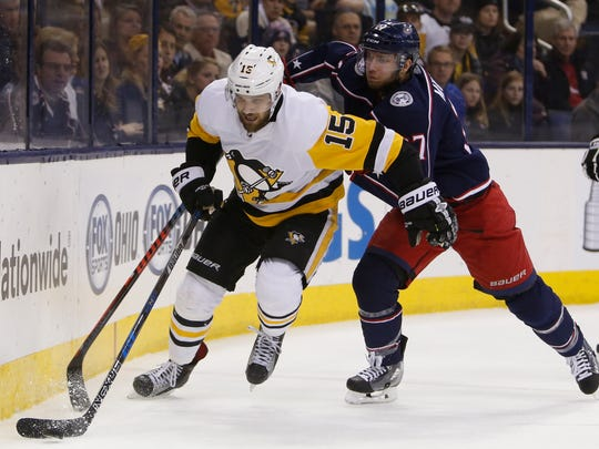 Pittsburgh Penguins' Riley Sheahan, left, and Columbus Blue Jackets' Ryan Murray chase the puck during the first period of an NHL hockey game Thursday, April 5, 2018, in Columbus, Ohio. (AP Photo/Jay LaPrete)