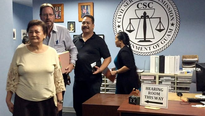In this Aug. 22 file photo Mark Charfauros, third from left, leaves the Civil Service Commission office.
