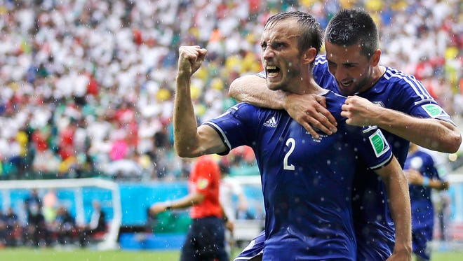 Bosnia's Avdija Vrsajevic (2) celebrates with teammate Vedad Ibisevic after scoring his team's third goal during the group F World Cup soccer match between Bosnia and Iran at the Arena Fonte Nova in Salvador, Brazil, Wednesday, June 25, 2014.