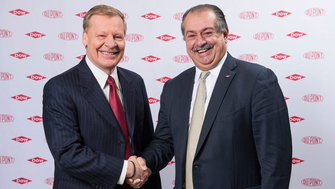 DuPont Chief Executive Ed Breen (left) shakes the hand of Dow Chemical Chief Executive Andrew Liveris in December 2015 after the two companies agreed to pursue a merger.