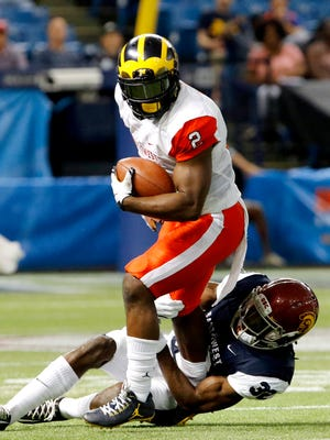 East's De'Veon Smith of Michigan drags a West defender after making a catch in the fourth quarter during the East-West Shrine Game at Tropicana Field on Saturday in St. Petersburg, Fla.
