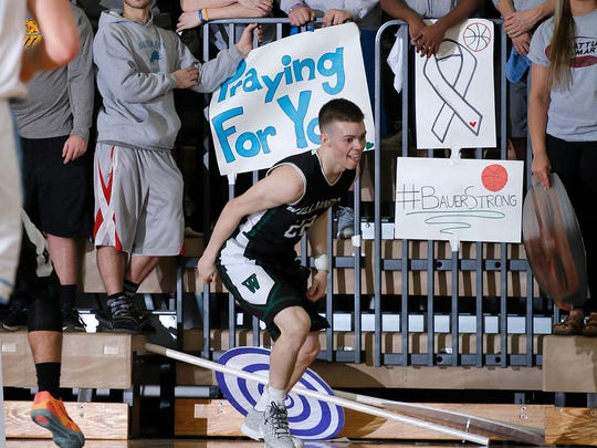 Williamston's Riley Lewis reacts after hitting a shot in front of the Lansing Catholic student fans, who wore gray and had signs with messages of support for Williamston coach Jason Bauer, Friday, March 11, 2016, at Fowlerville High School. Williamston won 70-60.