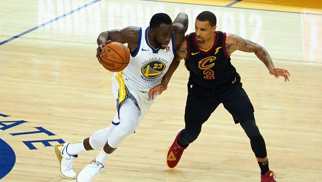Golden State Warriors forward Draymond Green (23) moves the ball against Cleveland Cavaliers guard George Hill (3) during the second half in game one of the 2018 NBA Finals at Oracle Arena.