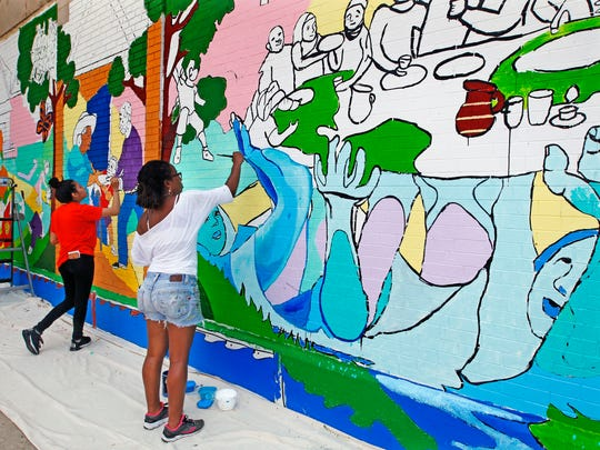 Tia Richardson and one of her students, Melissa Figueroa (left), work on a new community mural at El Rey Foodmart. The mural should be completed at the end of July.