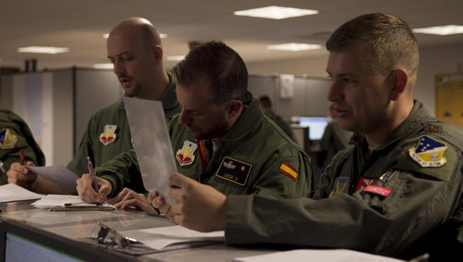 Maj. Aaron, a 29th Attack Squadron MQ-9 Reaper instructor pilot, right, Maj. Jaime, a Spanish air force student pilot, middle, and Staff Sgt. Francisco, a Spanish air force student sensor operator, left, review MQ-9 information at the step desk prior to a flight, at Holloman Air Force Base, N.M. on April 5, 2017. Spain is currently participating in essential training here at the MQ-9 formal training unit.