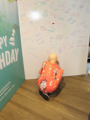 A patient signs a giant birthday card at Nemours Children's Specialty Care's 20th birthday celebration.