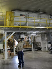 Assistant Manager and Purchaser Dean Haseman points to a large elevated mixer, used to blend tailored batches of feed.