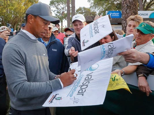 Tiger Woods signs autographs following the first round of the Valspar Championship golf tournament Thursday, March 8, 2018, in Palm Harbor, Fla. (AP Photo/Mike Carlson)