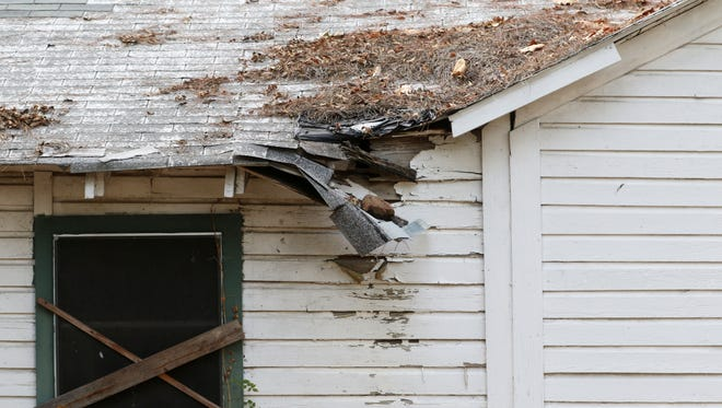 Shingles on the roof of house in Monroe dangle from the rotting roof of the abandoned home on Tuesday, Oct. 25, 2016. The house was one of six properties the city council voted to condemn as part of the city's effort to fight the blight. When issues such as these on a private property pose a health or safety hazard, there are a series of steps the Bossier Parish Police Jury must follow before any action can be taken.