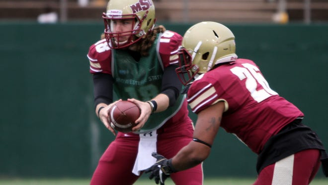 MSU Maroon quarterback Layton Rabb hands the ball off to Nicholas Gabriel in last year's Maroon and Gold Spring Game at Memorial Stadium. The duo will once again play together on the Maroon tam in Saturday's game.