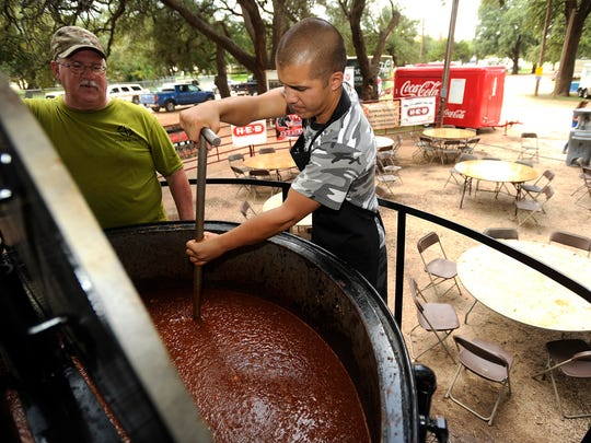 Garrett Jue (right) stirs the giant chili pot while talking with Frank Johnson while cooking in preparation for last year's Chili Super Bowl. The giant pot of chili is not part of the cookoff, but it made to sell. Last year, cooks used 1,500 pound of ground beef, 250 pounds of onions as well as lots of spices and tomato sauce to make 480 gallons of chili.