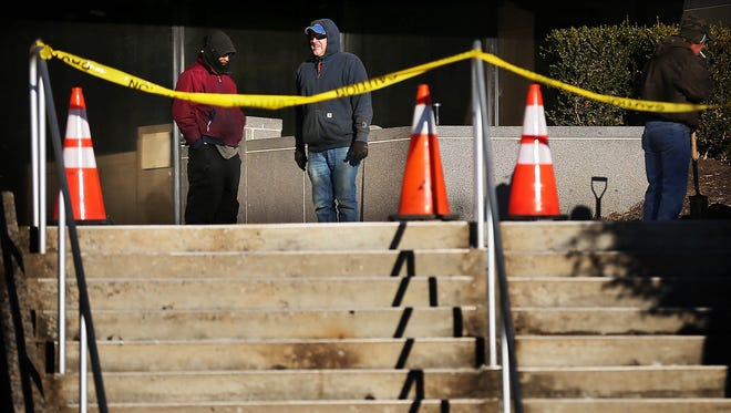 Workers prepare a cleanup effort after a pipe to the sprinklersystem at the Memphis Light, Gas and Water headquarters burst late Wednesday, spilling water onto the sidewalk and Second Street in Downtown.