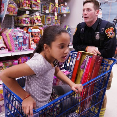 Firefighter Michael Thoms helps a child pick out Christmas