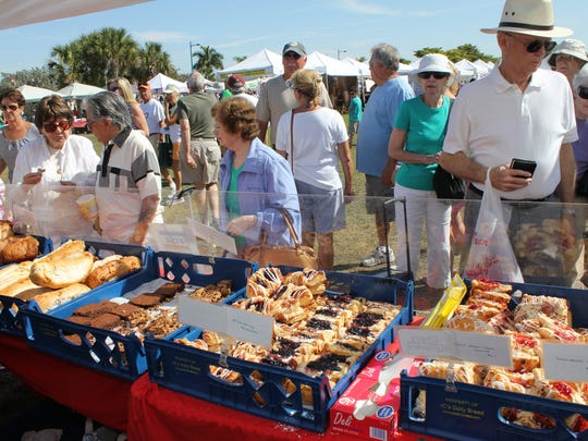 Customers peruse and taste the wide variety of breads