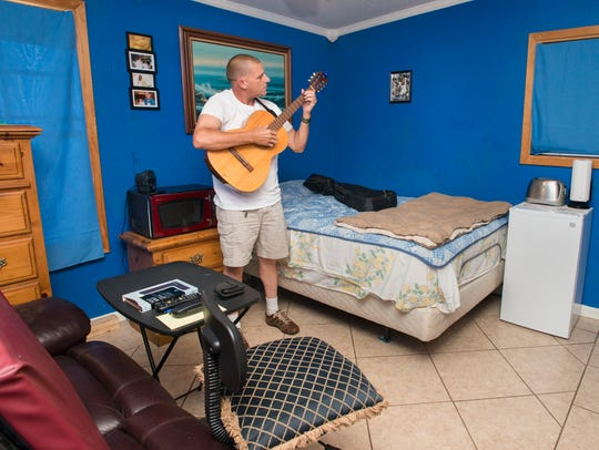 Art Smith plays his guitar in the room that he rents