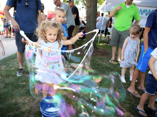 Scarlett Holscher, 3, of Ankeny makes giant bubbles
