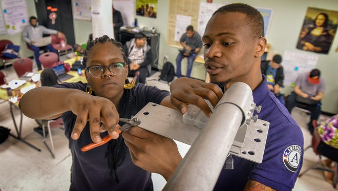 Pre-apprentices Melissa Simpson  and Kevin Joyner work at the Science Leadership Academy in the center city of Philadelphia and are learning to fix fixes laptops, software and smartboard issues, or in this case, remounting a repaired classroom projector.