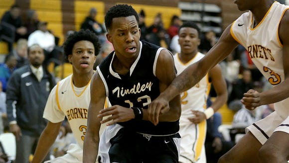 Tindley's Eric Hunter (13) drives by Howe's David Burns