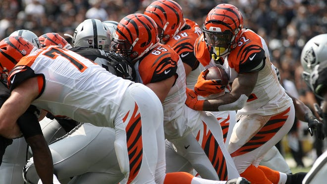 Cincinnati Bengals running back Jeremy Hill, right, breaks through the line of scrimmage for a touchdown in the second quarter during the Bengals' blowout win over the Raiders on Sept. 13.
