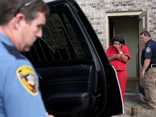 Latasha Lenard is escorted from the Madison County Justice Court in Madison County Thursday. Lenard is suspected of child abuse and neglect.