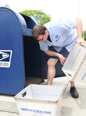 James Parsons, 29, a USPS letter carrier from the City of Poughkeepsie, empties the collection box outside of the City of Poughkeepsie Post Office on Mansion Street.