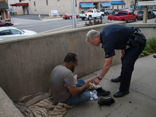 Loveland Police Sgt. Bob Shaffer checks on a homeless man, looking over his feet which are damaged due to walking in waterlogged shoes July 21 in downtown Loveland. Shaffer suggested the man stay off his feet until they and his shoes were dry to avoid further damage.
