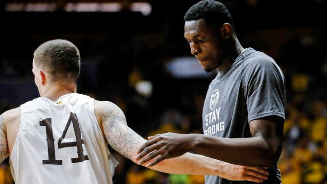 Wyoming Cowboys guard Josh Adams (14) and CSU Rams forward Emmanuel Omogbo (right) share words before the game at Arena-Auditorium. The Cowboys beat the Rams 83-76.