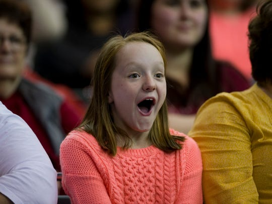 Megan Stewart, 10, of Evansville reacts to a party dress being modeled during Magic Moments' fashion show at the Wedding & Prom Expo at the Old National Events Plaza Sunday afternoon.