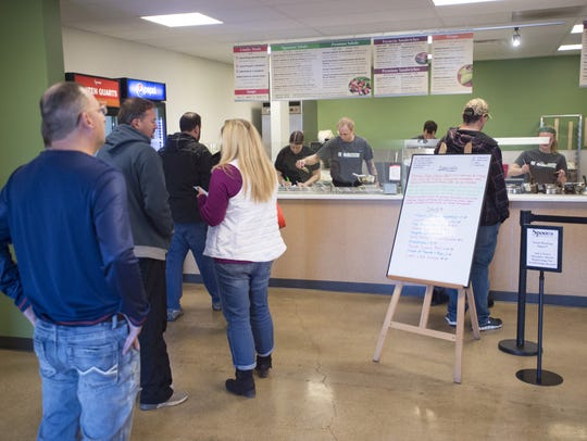Customers line up during the lunch rush at Spoons on