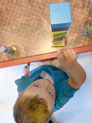 Nicholas Crawford stacks blocks on Tuesday during kindergarten camp at the Springmill Learning Center.