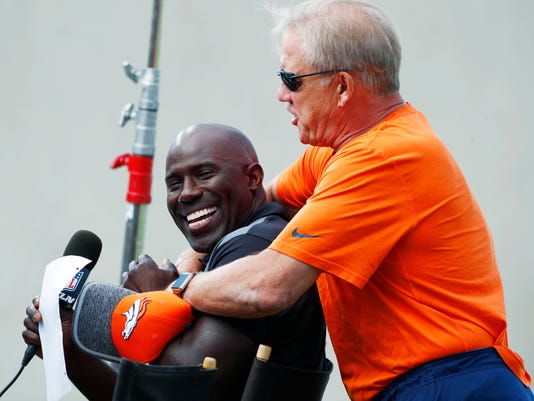 Denver Broncos general manager John Elway, right, hugs former teammate and NFL Hall of Fame inductee for 2017, Terrell Davis, as he waits to interview Elway for a television spot during drills at an NFL football training camp Sunday, July 30, 2017, in Englewood, Colo. (AP Photo/David Zalubowski)