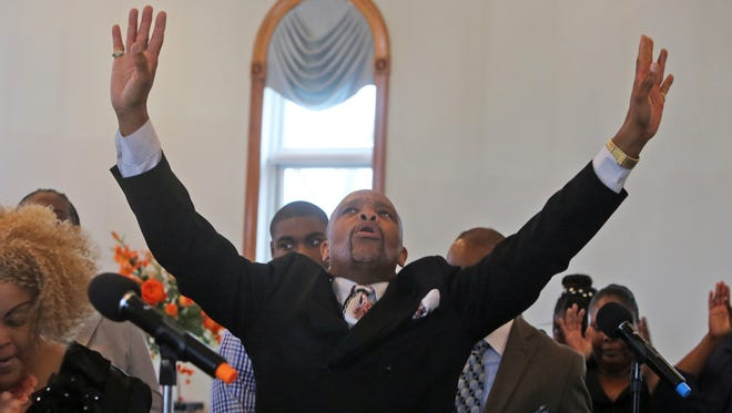 Wesley King a member of the choir at the Saint John Deliverance Tabernacle in Nyack, raises his arms in praise as the choir performs during the Sunday service.