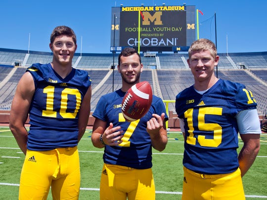 Michigan quarterbacks Zach Gentry (10), Shane Morris (7), and Jake Rudock (15) pose for a photo  in Michigan Stadium during the NCAA college football team's annual media day in Ann Arbor, Mich., Thursday, Aug. 6, 2015.