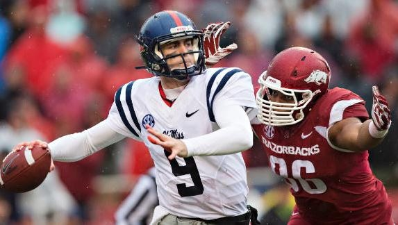 Ole Miss quarterback Ryan Buchanan tries to throw under pressure against Arkansas.
