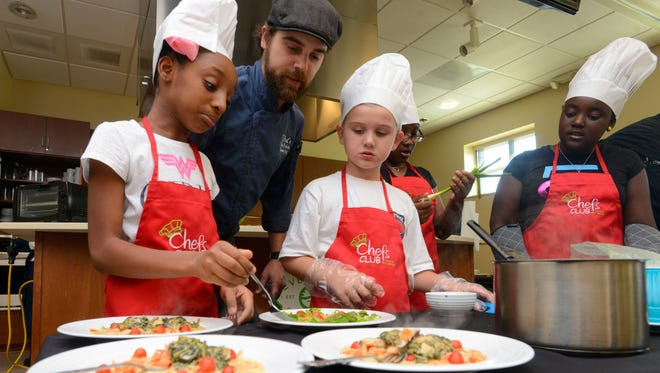 Ziah Peazant, Chef Chris Pichotta and Aiden Pelletier plate their food Sunday, May 7, 2017 during the Junior League of Pensacola Kids' Iron Chef Competition at Everman's Grocery Educational Center.