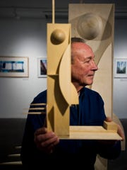 Tom Cullins holds a model sculpture that became 'De Stijl', constructed by Matthew Hastings of RIVEN to the exact scale, on display at the BCA Center.