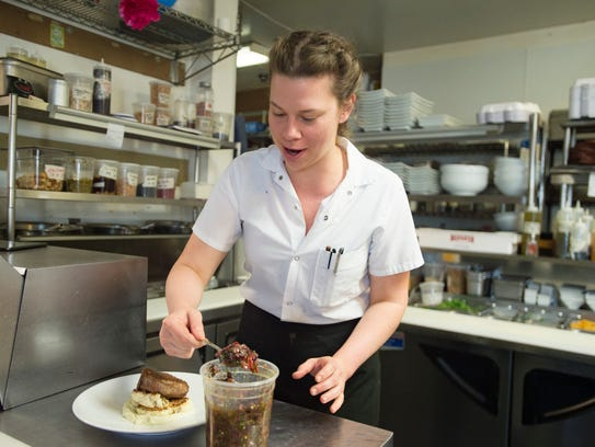 Brie Feilmeier plates a dish in the kitchen at Cafe