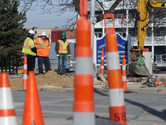 MDOT crew and construction workers stand at the corner of Water Street Monday, Jan. 25, while construction takes place at the intersection of Water and Military Streets in Port Huron.