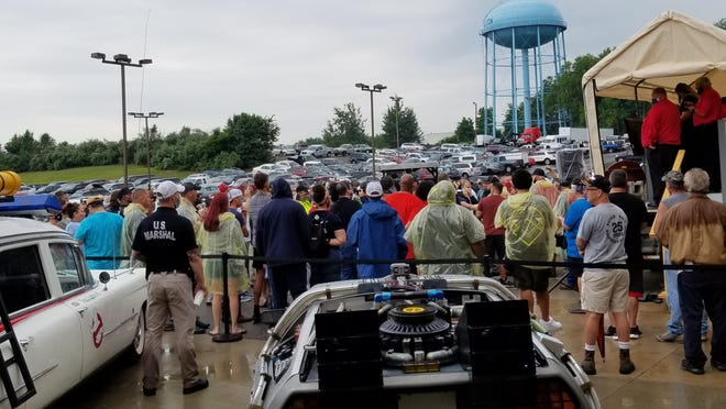 Hundreds gathered in person and online to take part in the auction as the U.S. Marshals Office sought new owners for three replica movie cars Saturday under rainy skies.