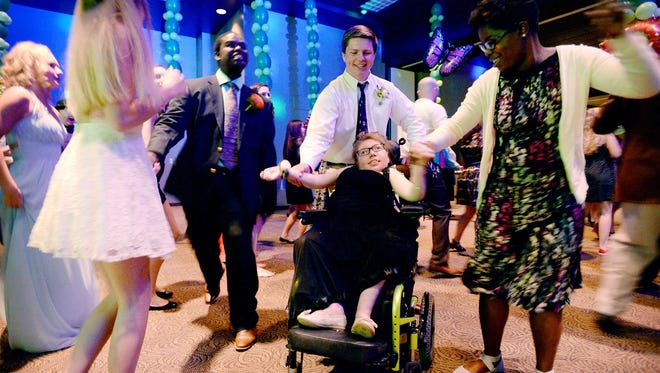 Erin Pickel and her date, T.C. Roberson freshman Joseph Scarborough, 15, dance with teaching assistant Nevada Brown during the PEP prom at Biltmore Baptist Church on Friday, April 15, 2016.