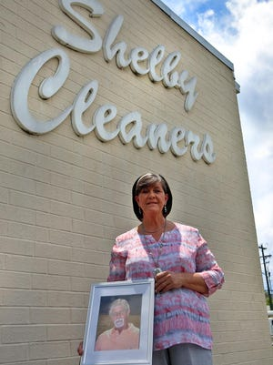 Denise McCullough holds a photo of her husband outside Shelby Cleaners on Thursday. McCullough is closing the business after 25 years of service.