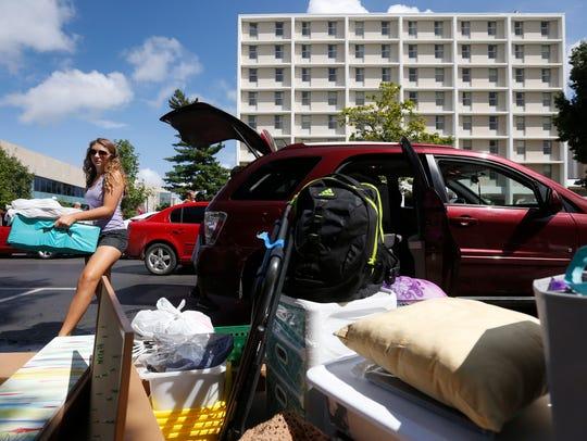 Freshman Jillian Hays unloads her belongings out of