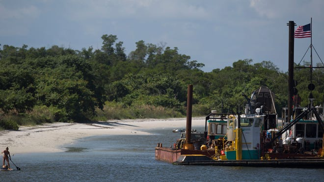 A paddleboarder makes her way by heavy equipment that is used in the dredging processes in Big Carlos Pass on Wednesday 10/1/2014. The renourishment is getting underway on Lovers Key. A project to renourish the north end of Bonita Beach was recently completed.