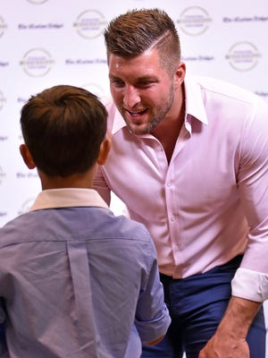 Tim Tebow shakes hands with a fan Thursday night at the Best of MS Preps at the Jackson Convention Center.