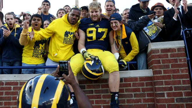 Michigan cornerback Raymon Taylor takes a picture of teammate Brennen Beyer (97) with fans in the student section after Michigan's 34-10 win over Miami (Ohio) in Ann Arbor on Sept. 13, 2014.