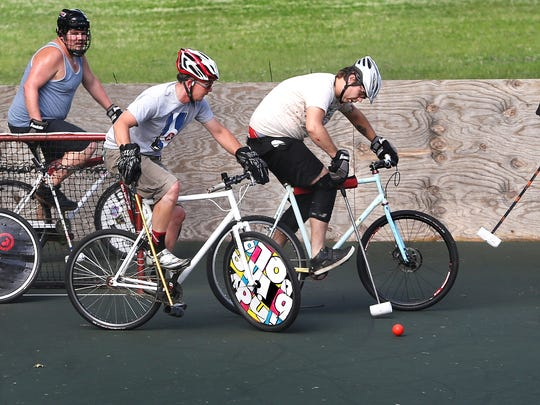 Jeff Kelly, right, moves toward the ball controlled by Tucker Schwinn, second from right, during the Indy Bike Polo team's practice on a court in Arsenal Park at 46th and Haverford on Tuesday, July 1, 2014. Others show are, from left, Kyle Roland, Nick Nacrelli and Evan Cromer.